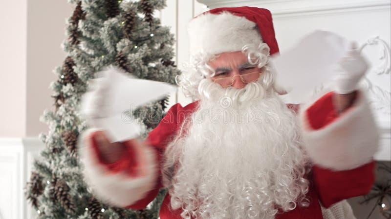 Santa Claus enojada que lee una letra y que la rasga aparte fotos de archivo libres de regalías