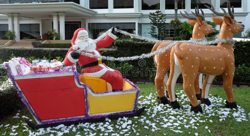 Santa Claus entrega los regalos en un trineo dibujado por el reno, escultura decorativa del jardín, a foto de archivo