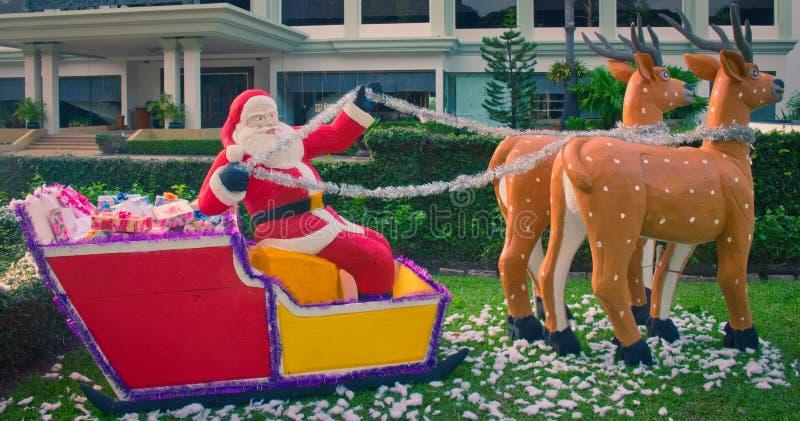 Santa Claus entrega los regalos en un trineo dibujado por el reno, escultura decorativa del jard?n, la Navidad del verano fotos de archivo