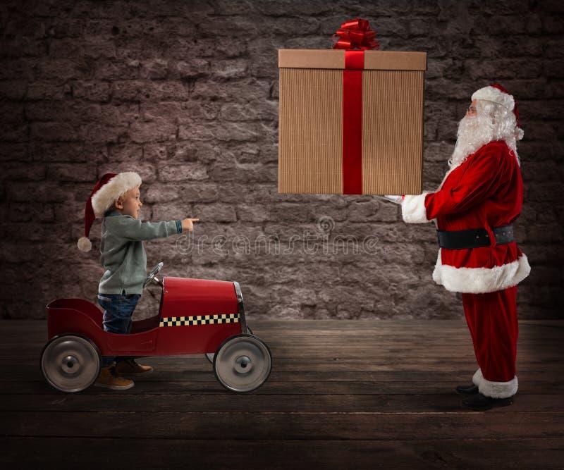 Santa Claus entrega um presente do Natal a uma criança imagens de stock royalty free