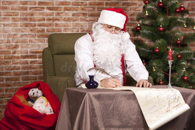Santa Claus escribe su lista fotografía de archivo libre de regalías