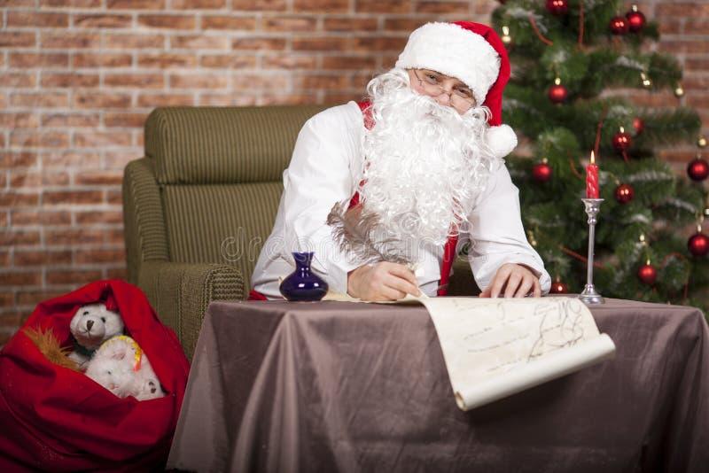 Santa Claus escribe su lista imágenes de archivo libres de regalías