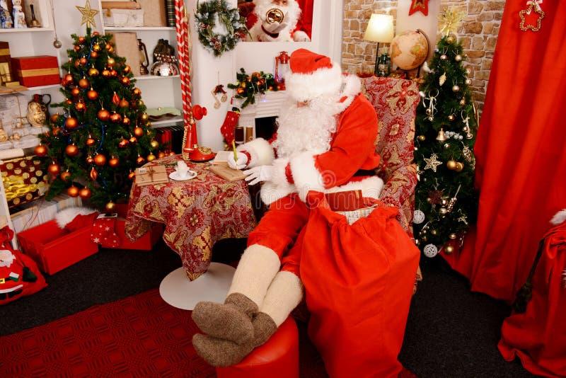 Santa Claus está preparando presentes para o Natal foto de stock