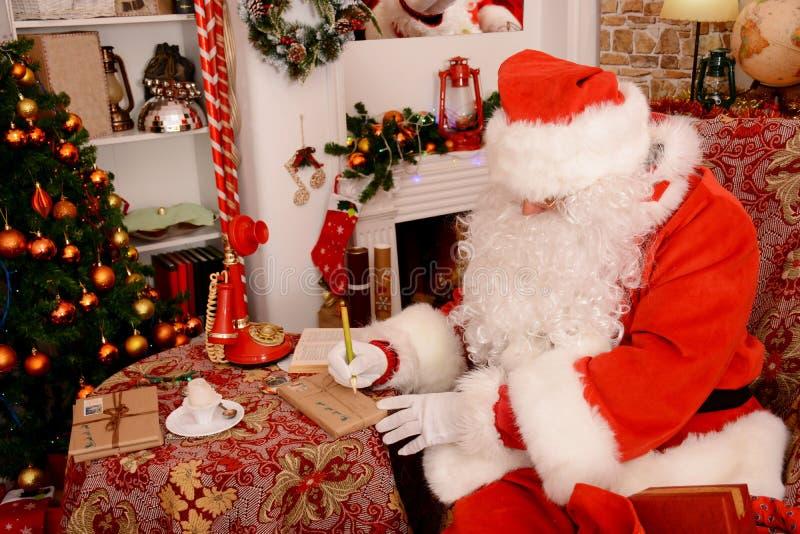 Santa Claus está preparando presentes para o Natal fotografia de stock