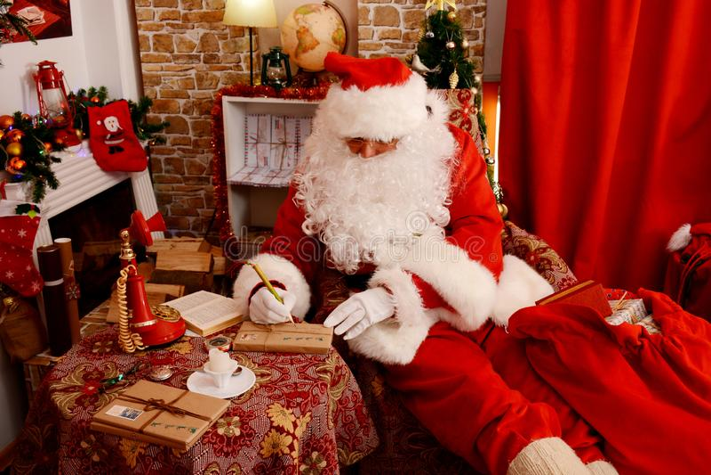 Santa Claus está preparando presentes para o Natal imagens de stock royalty free