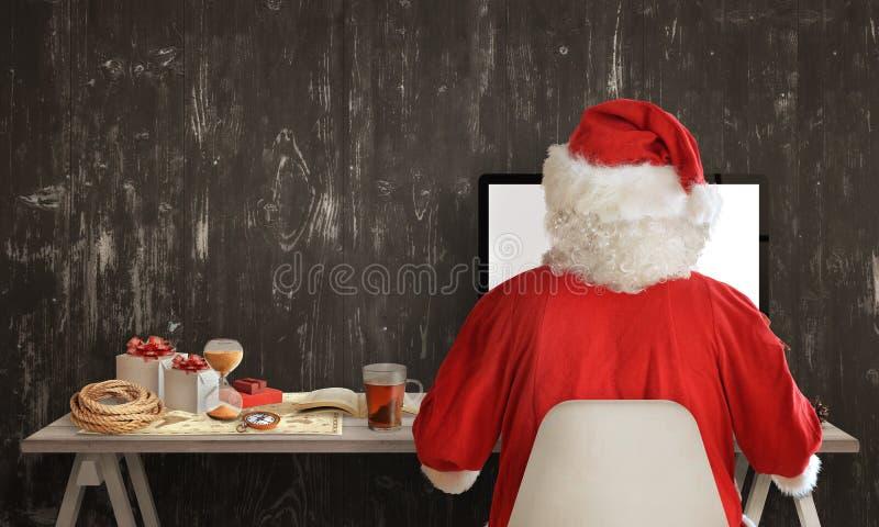 Santa Claus está preparando-se para uma viagem e está compartilhando-se de presentes no computador fotos de stock royalty free