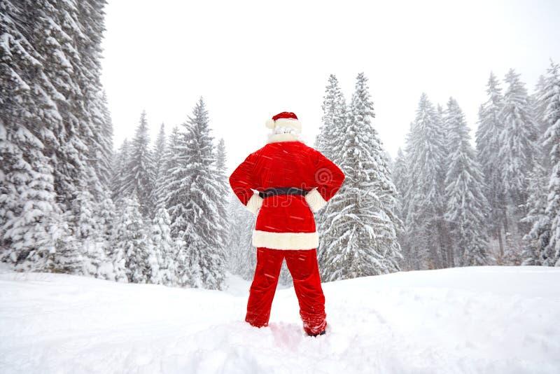 Santa Claus está retrocediendo la visión en el bosque en el invierno a imagenes de archivo