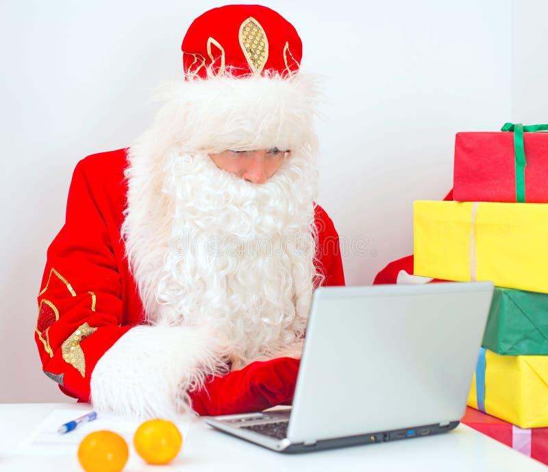 Santa Claus está usando o portátil fotos de stock