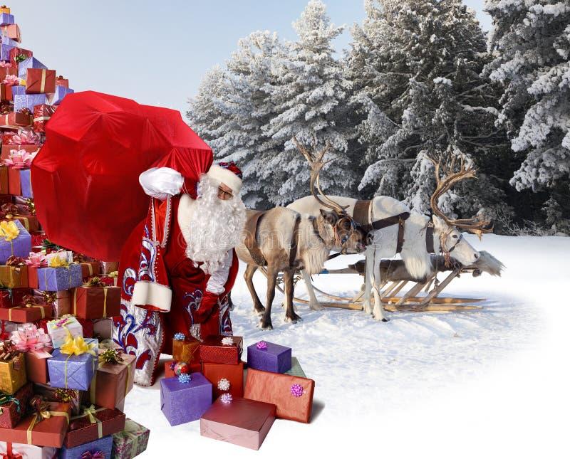 Santa Claus et son renne avec des cadeaux images stock