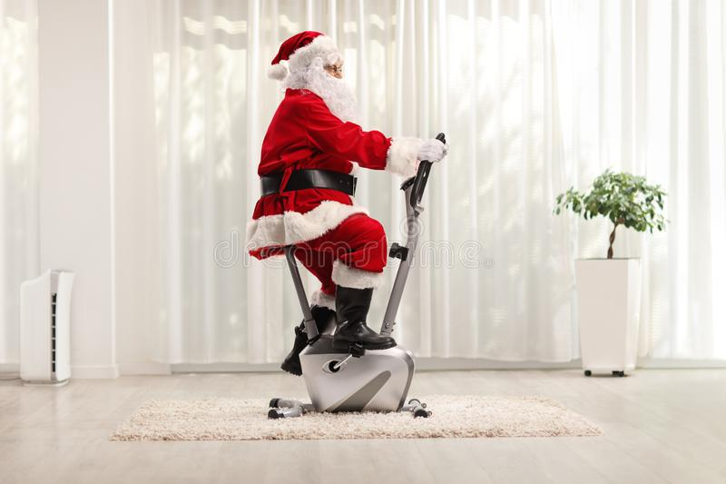 Santa Claus exercising on a stationary bicycle stock images