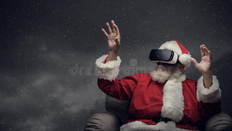 Santa Claus experiencing virtual reality. Surrounded by snow falling, he is wearing VR glasses and interacting with a virtual environment stock photos
