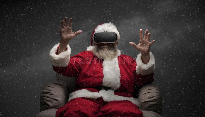 Santa Claus experiencing virtual reality. He is wearing VR glasses and interacting with a virtual environment stock photo