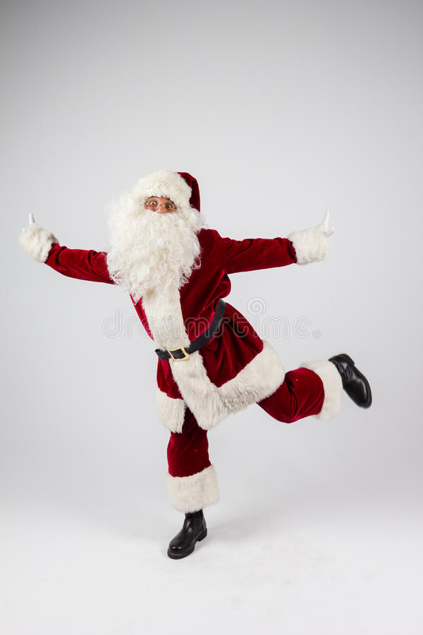 Santa Claus in eyeglasses and red costume dancing on white background and looking into camera. royalty free stock image