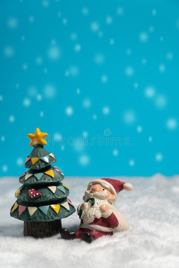 Santa Claus felice con il contenitore di regali che si siede sulla neve vicino all'albero di Natale fotografia stock libera da diritti