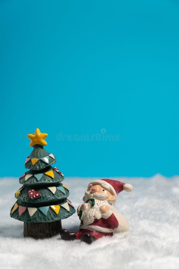 Santa Claus felice con il contenitore di regali che si siede sulla neve vicino all'albero di Natale fotografia stock