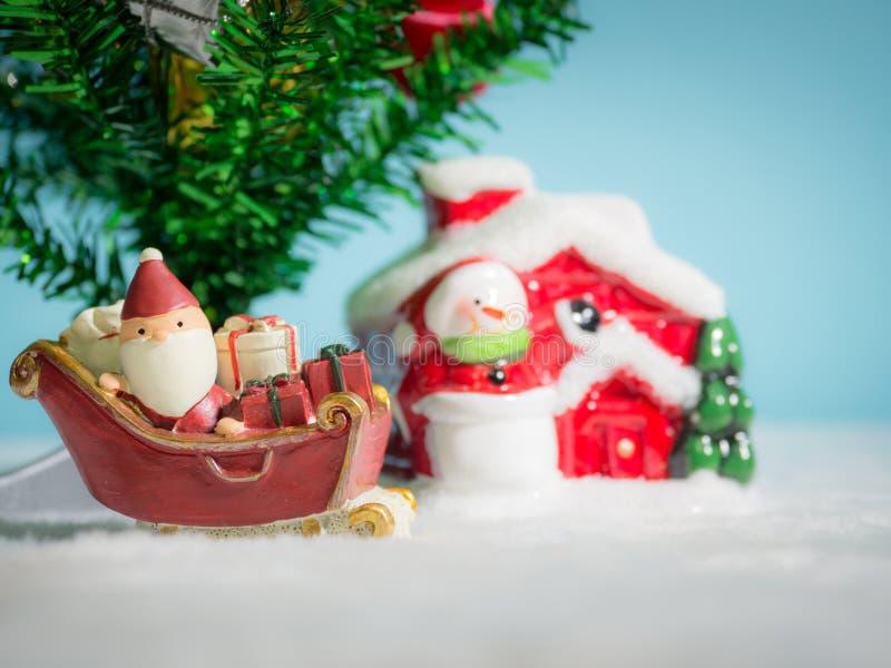 Santa Claus felice con il contenitore di regali sulla slitta della neve che va alloggiare vicino alla casa abbia il pupazzo di ne immagine stock libera da diritti