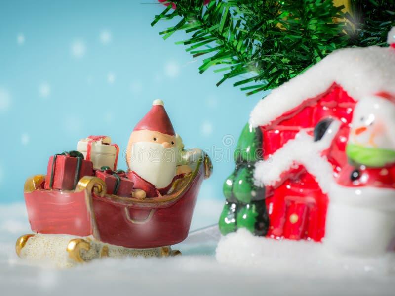 Santa Claus felice con il contenitore di regali sulla slitta della neve che va alloggiare vicino alla casa abbia il pupazzo di ne fotografie stock