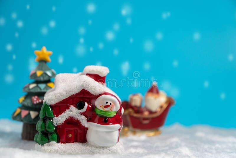 Santa Claus felice con il contenitore di regali sulla slitta della neve che va nevicare casa vicino alla casa della neve abbia il fotografia stock