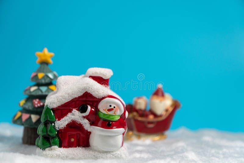 Santa Claus felice con il contenitore di regali sulla slitta della neve che va nevicare casa vicino alla casa della neve abbia il immagini stock libere da diritti