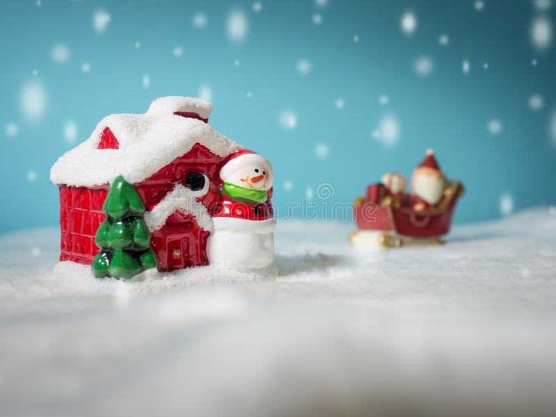 Santa Claus feliz con la caja de regalos en el trineo de la nieve que va a nevar casa cerca de casa de la nieve tenga el muñeco d imagen de archivo