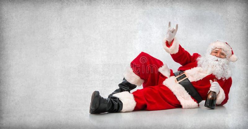 Santa Claus feliz que miente en el piso con una botella de vino fotografía de archivo