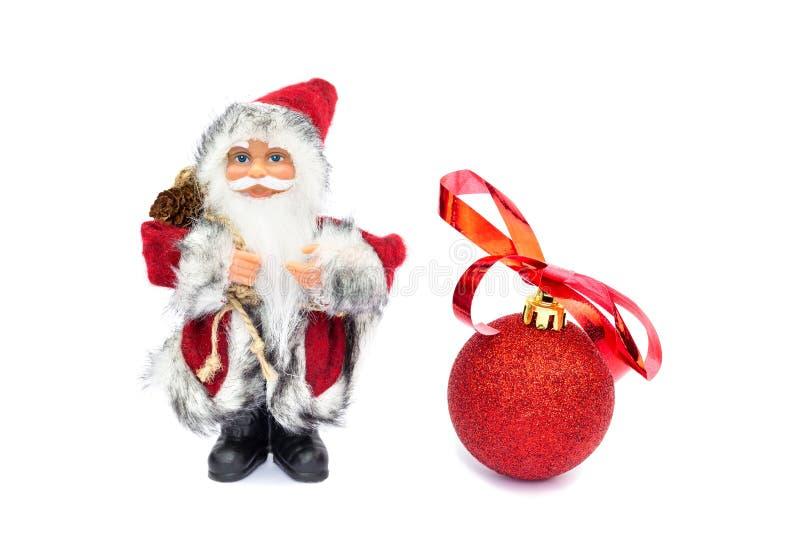 Santa Claus-Figürchen mit rotem Weihnachtsball auf Weiß stockfotos