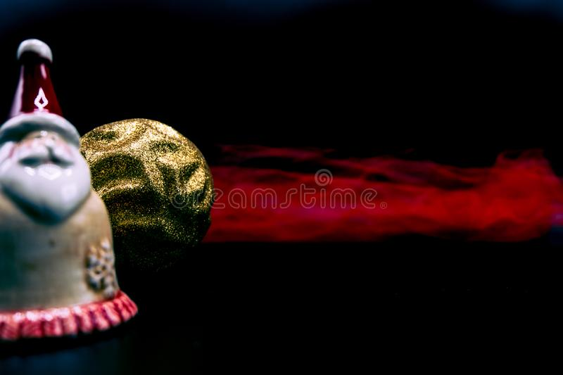 Santa Claus figure, golden glittered Christmas ball and red fabric on black. stock photo
