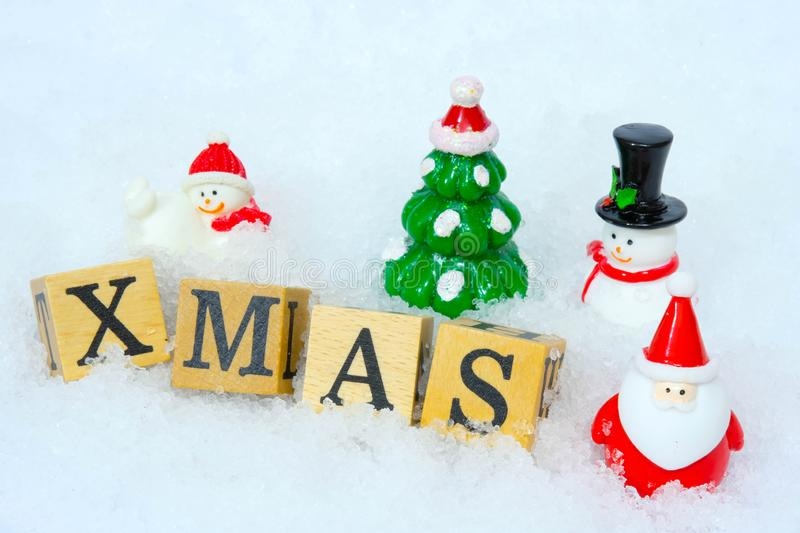 Santa Claus figure model and Christmas tree and Snowman with the wooden word  alphabet `XMAS` on the snow background stock image