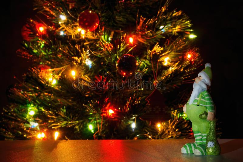 Santa Claus figurine in green clothes on background christmas tree with garland lights. Copy text, selective focus.  royalty free stock photo