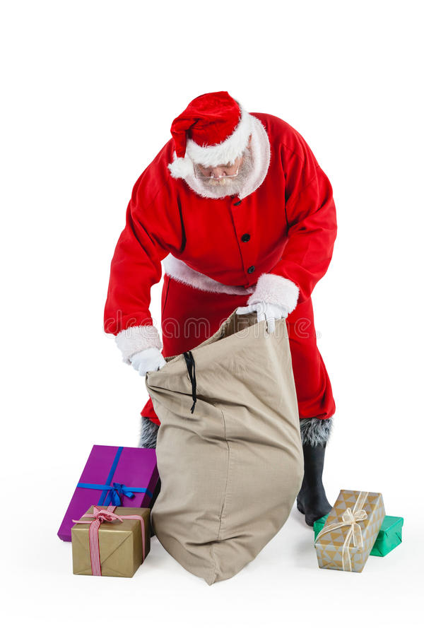 Santa claus filling gift boxes in the sack stock photos