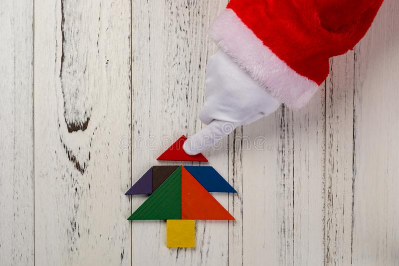 Santa claus finishing the last bit of Christmas tree made by tangram royalty free stock photo
