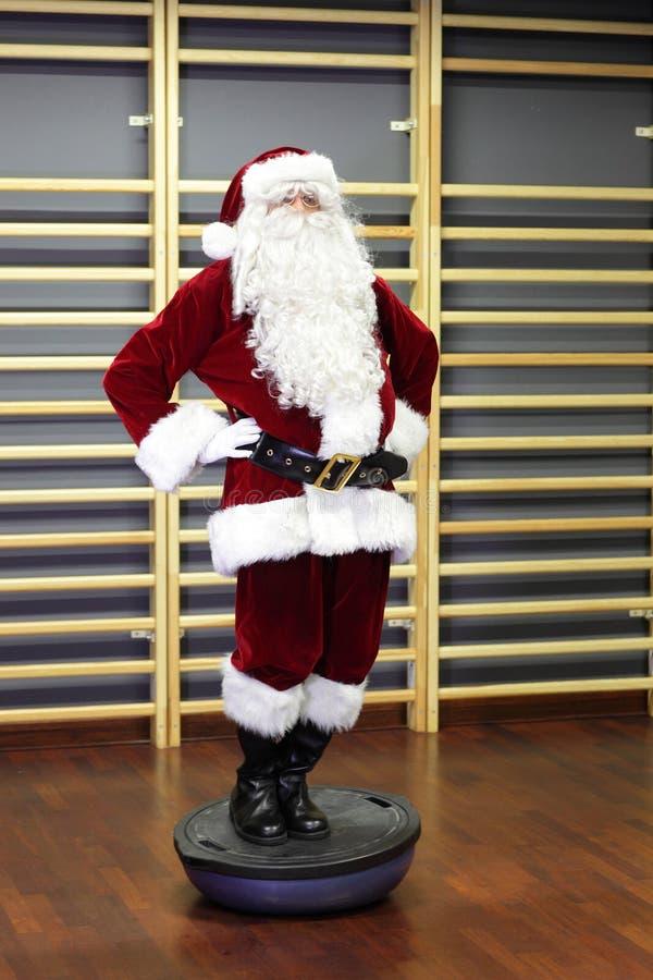 Santa Claus Fitness utbildning på stablityhalvklot royaltyfri fotografi