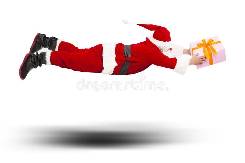 Santa Claus flyg som levererar en gåvaask royaltyfria bilder
