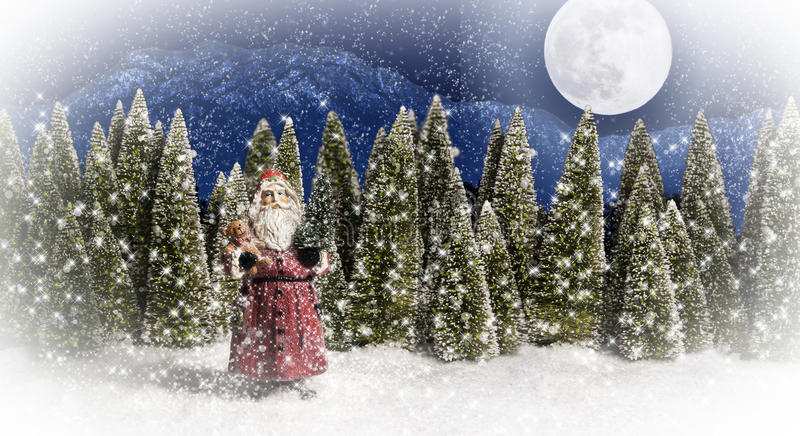 Santa Claus Forest Moon 2. Santa Claus carrying an evergreen tree and teddy bear toy standing in snow with forest trees, mountain, and moon in background stock photography