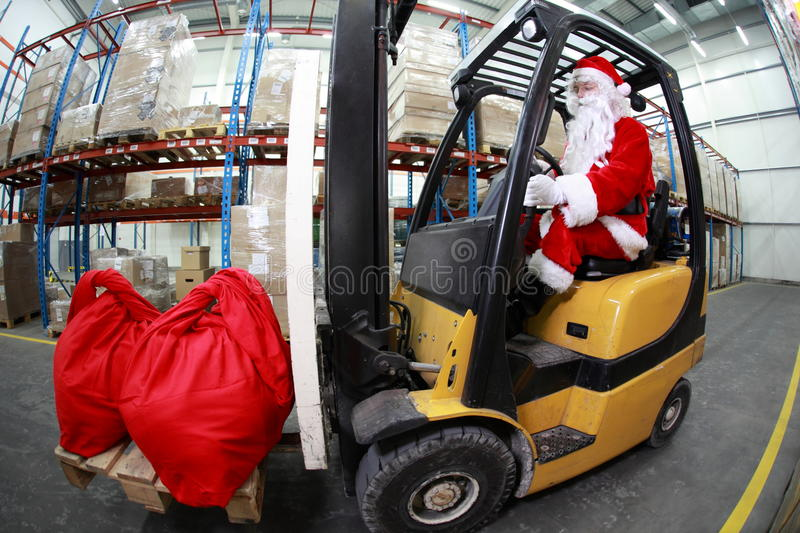 Santa Claus forklift operator in warehouse. Santa Claus as a forklift operator at work in warehouse. 2 large red sack at the front of forklift.fish-eye lens royalty free stock images
