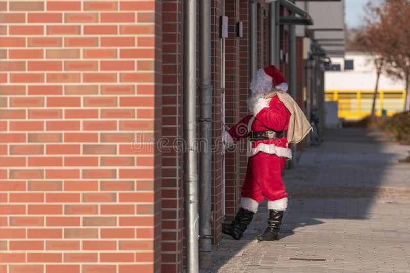 A Santa Claus at a front door in the city royalty free stock photography