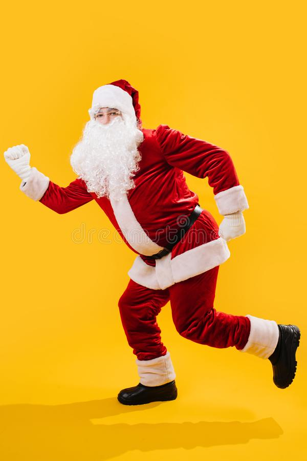 The Santa claus froze in runner pose. Santa Claus froze in runner pose isolated on yellow background. Xmas concept royalty free stock photography