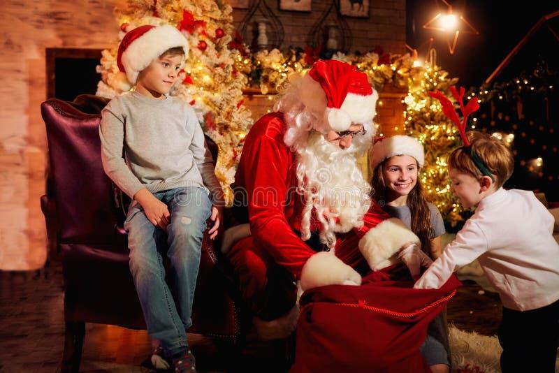 Santa Claus geeft voorstelt aan kinderen op Kerstmisdag stock foto