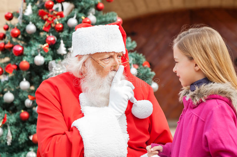 Santa Claus Gesturing Finger On Lips mientras que mira fotos de archivo