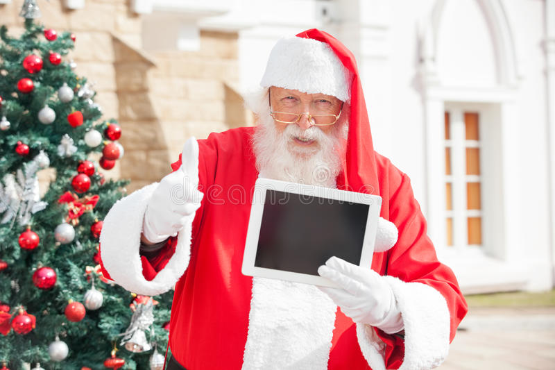 Santa Claus Gesturing Thumbsup While Holding stock images