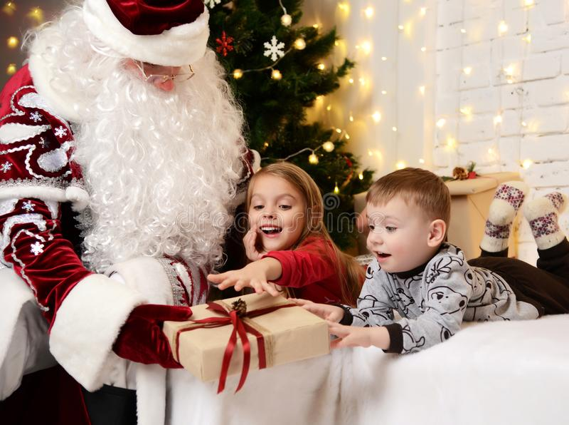 Santa Claus-geven huidig aan een gelukkig klein leuk kinderenjongen en een meisje dichtbij Kerstboom royalty-vrije stock foto's