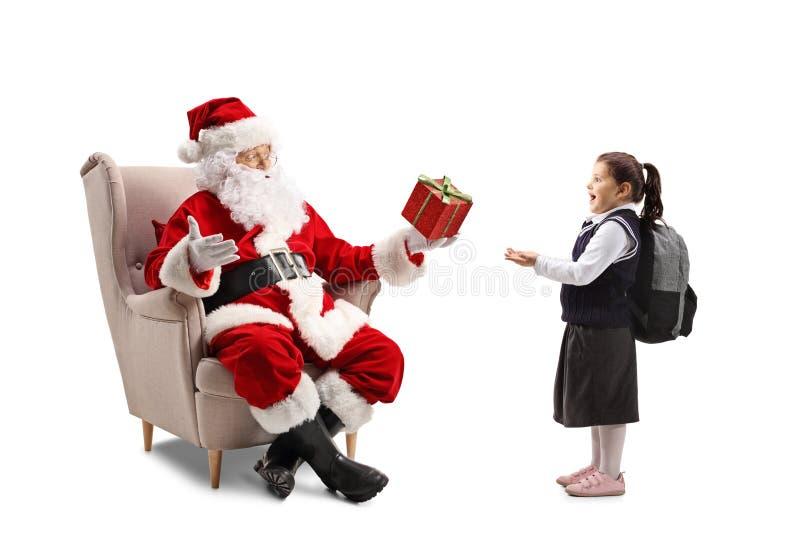 Santa Claus gezet in een leunstoel die een heden geven aan verrast weinig die schoolmeisje op witte achtergrond wordt geïsoleerd royalty-vrije stock foto