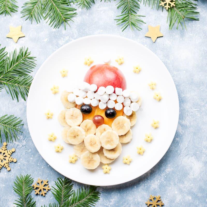 Santa Claus-gezicht van vruchten en heemst op een plaat wordt gemaakt die Kerstmisvoedsel voor kinderen Hoogste mening stock foto