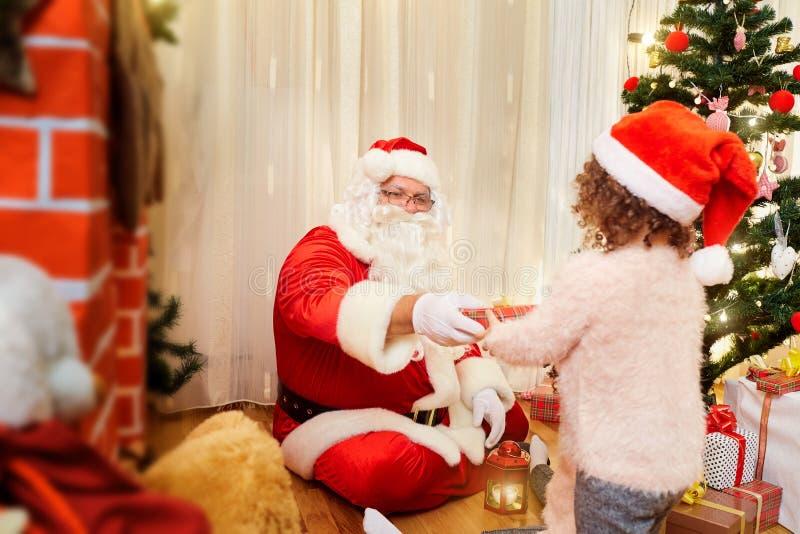 Santa Claus gibt dem Kind ein Geschenk für Weihnachten zuhause in einem ro lizenzfreie stockbilder