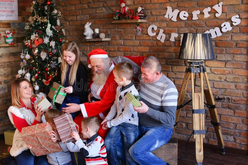 Santa Claus gibt der großen Familie in verziertem Raum Neujahrsgeschenke lizenzfreie stockfotos