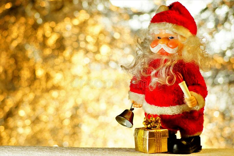 Santa Claus with a gift on the background of Christmas lights bokeh. Santa Claus is a fairy-tale character who gives gifts. To children for Christmas. Winter royalty free stock photo