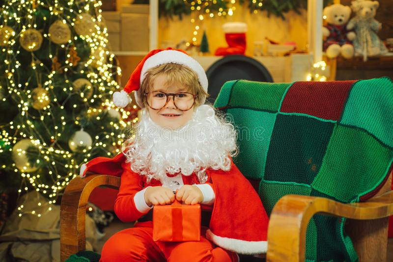 Santa Claus with a gift for children. Christmas and New Year. Happy child holds a gift in red packaging. Happiness royalty free stock photo