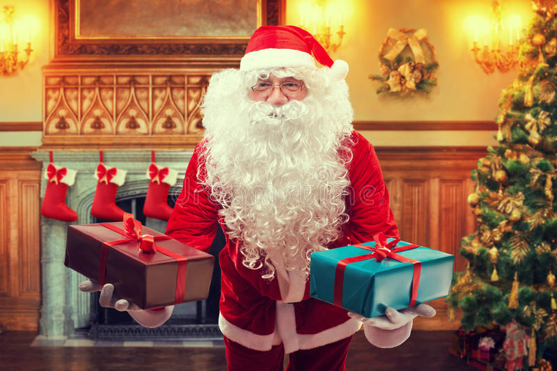 Santa Claus with gifts. In decorated living room stock images