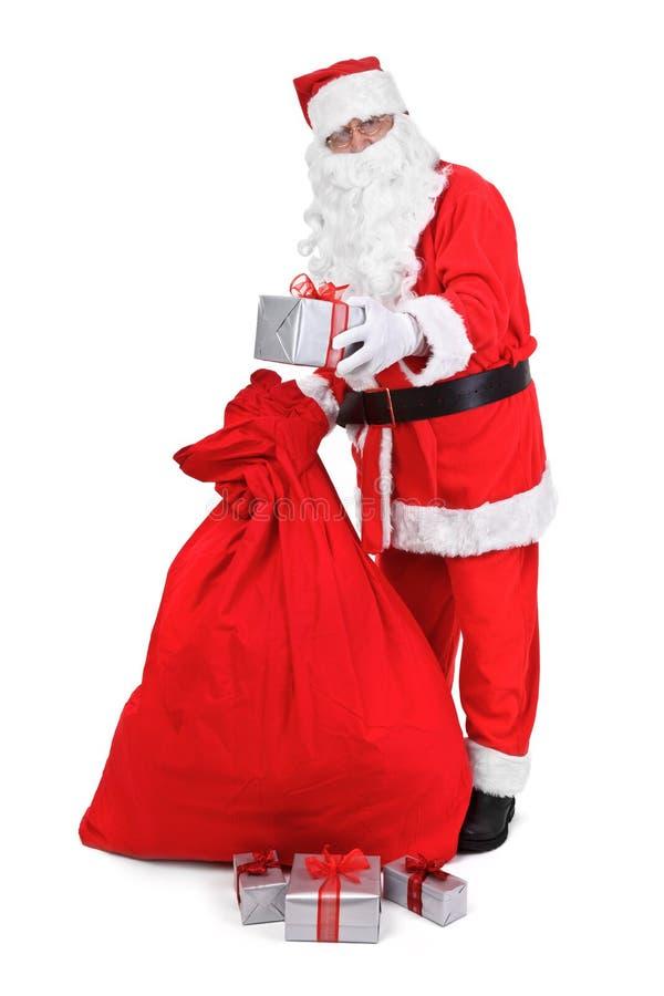 Santa claus gives a present royalty free stock photo
