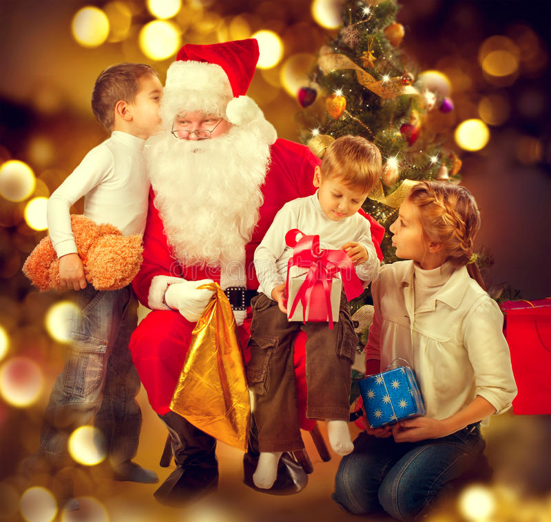 Santa Claus giving Christmas gifts to children. Christmas holiday scene stock photo